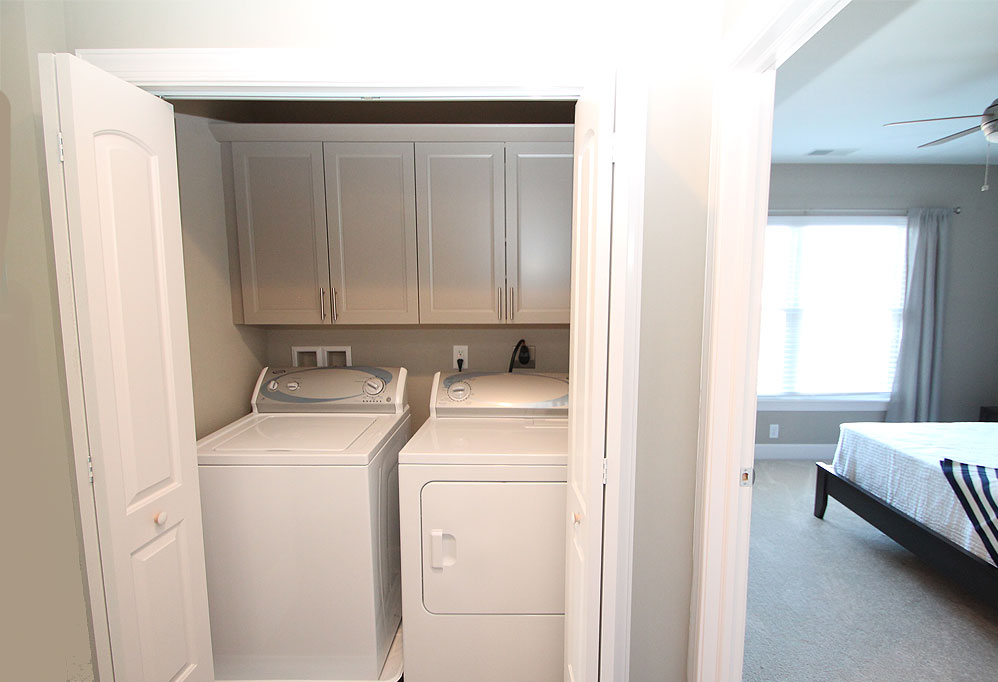 Custom laundry room storage in a closet by Cabinetsmith